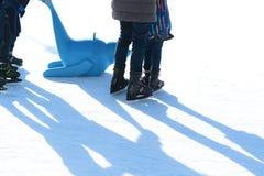 Familienspaß auf Eisbahn im Freien, Kind, das lernt, mit Plastikdichtung als Ausbildungshilfen eiszulaufen Stockfotografie