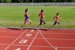 Familiensport und -eignung, glückliche Mutter und Kinder, die draußen auf Stadionsbahn, Kindergesunder aktiver Lebensstil laufen lizenzfreies stockbild