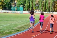Familiensport und -eignung, glückliche Mutter und Kinder, die draußen auf Stadionsbahn, Kindergesunder aktiver Lebensstil laufen stockbild