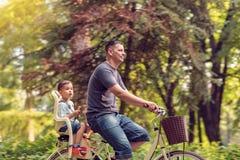 Familiensport und gesunder Lebensstil Vater- und Sohnreitfahrrad I Stockbilder