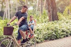 Familiensport und gesunder Lebensstilvater und -sohn, die ein bicy reitet Stockbild
