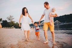 Familienurlaub im Sommer Junger kaukasischer Familienfu? barf??ig sandigen Strand, UferFlusswasser gehend Vatimutterh?ndchenhalte lizenzfreies stockbild