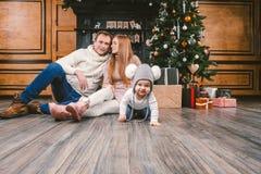 Familienurlaub-neues Jahr und Weihnachten Der junge kaukasische 1-jährige Familienmutter-Vatisohn sitzen Bretterboden nahe KaminW lizenzfreies stockfoto