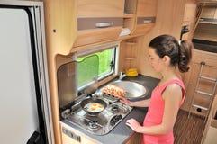 Familienurlaub, RV-Feiertagsreise, Reise und Kampieren, Frau, die im Camper, motorhome Innenraum kocht Lizenzfreie Stockfotos
