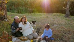Familienurlaub am Sonnenuntergang, an der älteren Frau mit dem Manngetränktee, der nahe Hund sitzt und am Enkel stock video