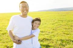 Familienvater und -kind, die auf Wiese umarmen stockfotografie