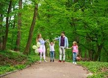 Familienvater und -mutter mit zwei Kindern, die in gr?nen Stadtpark des Sommers auf Picknick, frohe Feiertage Eltern und Kinder a lizenzfreie stockfotografie