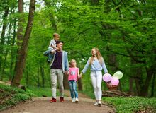 Familienvater und -mutter mit zwei Kindern, die in gr?nen Stadtpark des Sommers auf Picknick, frohe Feiertage Eltern und Kinder a stockbilder