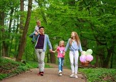 Familienvater und -mutter mit zwei Kindern, die in gr?nen Stadtpark des Sommers auf Picknick, frohe Feiertage Eltern und Kinder a lizenzfreies stockbild