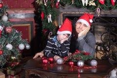 Familienvater und -sohn traurig auf Weihnachtsabend Lizenzfreie Stockfotografie