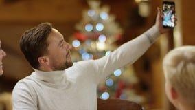 Familienvorstand nimmt Gruppe selfie mit seiner Familie durch Weihnachtstabelle, Abschluss oben stock video