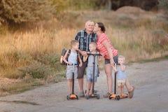 Familienweg auf Rollern mit seiner Frau und Kindern auf der Dorfstraße nahe Wolgograd stockbild
