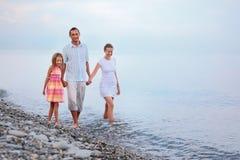 Familienweg auf Strand im Abend, Fokus auf Mutter Lizenzfreie Stockfotografie