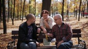 Familienweg im Park Die Verbindung zwischen Generationen Erwachsener Sohn, der mit älteren Eltern im Herbst Park spricht stock footage