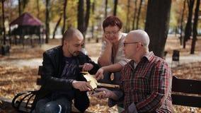 Familienweg im Park Die Verbindung zwischen Generationen Erwachsener Sohn, der mit älteren Eltern im Herbst Park spricht stock video