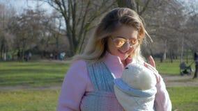 Familienweg, junges Elternteil mit Gläsern liegt beim Sohn im Riemen im Park im warmen Wetter stock footage