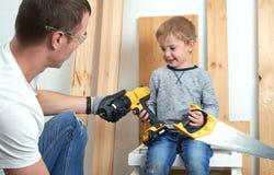 Familienzeit: Vati zeigt seine Sohnhandwerkzeuge, einen gelben Schraubenzieher und eine Metallsäge Sie müssen Bretter für bohren  lizenzfreies stockbild