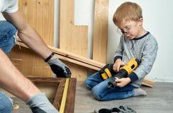 Familienzeit: Vati zeigt seine Sohnhandwerkzeuge, einen gelben Schraubenzieher und eine Metallsäge Sie müssen Bretter für bohren  lizenzfreie stockfotografie