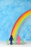 Familiepictogrammen met een regenboog en een blauwe hemel Stock Afbeeldingen