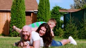 Familieportret in het park, vader die, moeder, zoon, pretlach, op het gazon, gelukkige familie liggen die het weekend doorbrengen stock video