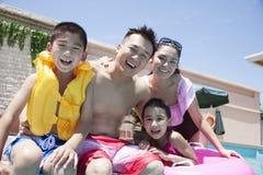 Familieportret, moeder, vader, dochter, en zoon, die door de pool glimlachen Stock Afbeelding