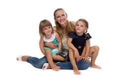Familieportret van een jonge charmante moeder en twee dochters Stock Afbeeldingen