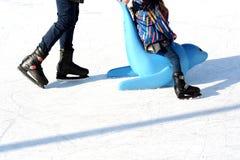 Familiepret op openluchtijsbaan, jong geitje die met plastic verbinding als opleidingshulp leren te schaatsen Royalty-vrije Stock Afbeeldingen