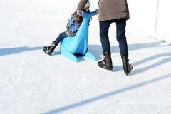 Familiepret op openluchtijsbaan, jong geitje die met plastic verbinding als opleidingshulp leren te schaatsen Stock Afbeelding