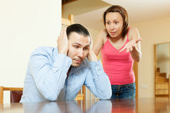 Familieruzie. Vermoeide mens die aan zijn boze vrouw luisteren Stock Foto