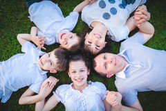 Families with children lying on the grass Stock Photo