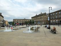 Families and children playing in the fountains in the pedestrian St. George`s Square in huddersfield yorkshire. Huddersfield, Yorkshire, England - Juiy 28 2018 royalty free stock photography