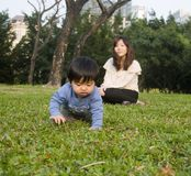 Families Chinese. Mom and son playing on the grass Royalty Free Stock Photography