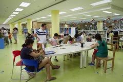 Families die in bibliotheek lezen stock afbeelding