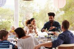 Families die van Openluchtmaaltijd op Terras samen genieten stock foto's