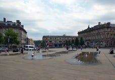 Families en kinderen die in de fonteinen in het voetst George ` s Vierkant in huddersfield Yorkshire spelen royalty-vrije stock afbeeldingen