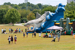 Families Enjoy A Giant Inflatable Shark Slide At Festival Playground Royalty Free Stock Photos