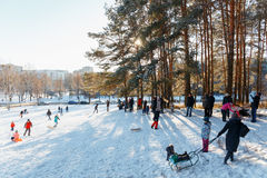 Families enjoy sledding on a snowy hill Stock Images