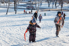 Families enjoy sledding on a snowy hill Stock Image