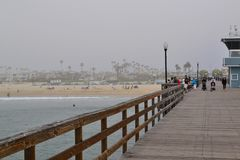 On pier looking back at the city of Seal Beach,CA. Families enjoying a walk on the pier in Southern California royalty free stock photo