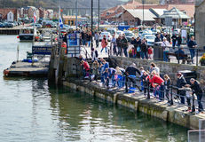 Families fishing for crabs in Whitby harbour Stock Photo