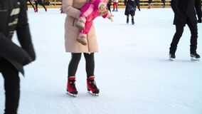 Families and friends enjoying skating on ice rink in winter