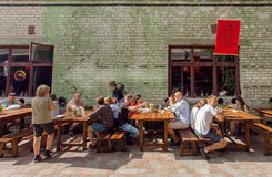 Families having dinner around tables outdoor during summer party Stock Photo