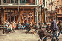 Families with kids meeting on streets, talking and drinking at outdoor bar with vintage furniture at evening. BRUSSELS, BELGIUM: Families with kids meeting on royalty free stock photos