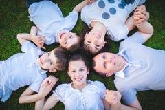 Families met kinderen die op het gras liggen Stock Foto