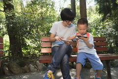 mom and kid playing smartphone stock images