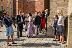 Families pose for pictures outside church. Neuoetting,Germany-June 22,2018: Families pose for pictures with their children outside the local church before Stock Image