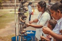 Families van het bidden van mensen die de olielampen aansteken dichtbij de Boeddhistische tempel Stock Foto