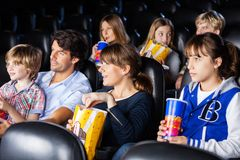Families Watching Movie In Cinema Theater. Families having snacks while watching movie in cinema theater stock photos