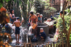 Families at the well. Hmong refugees in northern Thailand retrieve their rationed water from a shared well in camp,1980 Stock Photo