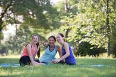 Families with young Russian mother and daughter are talk about e. Xercise. After practice yoga at the park finished. Health and Fitness concept royalty free stock image